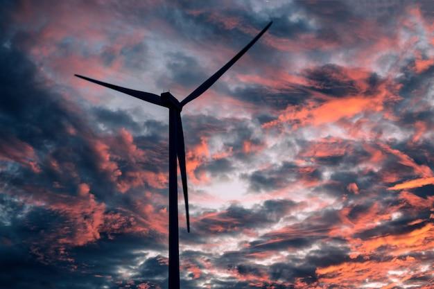 Siluetta nera delle turbine eoliche contro il cielo rosso