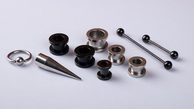 Pezzi di gioielli per l'orecchio neri e argento su sfondo bianco