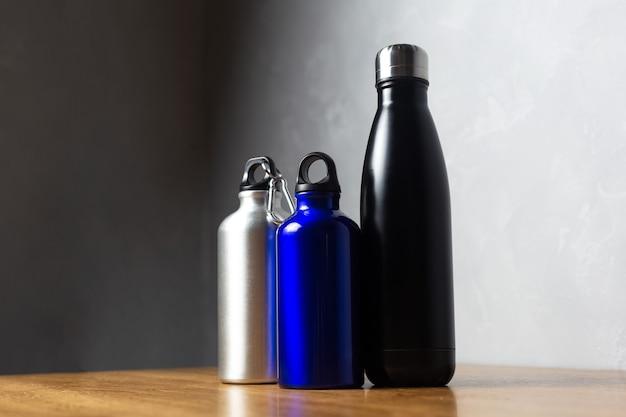 Bottiglie termiche nere, argento e blu oltremare sul tavolo di legno.