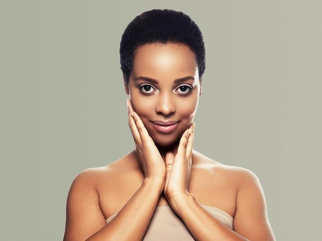 Pelle nera bellezza donna capelli sani pelle vicino afroamericano bellissimo modello con le mani. sul grigio.