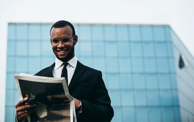 Un uomo dalla pelle nera legge il giornale davanti allo specchio. uomo d'affari in pausa