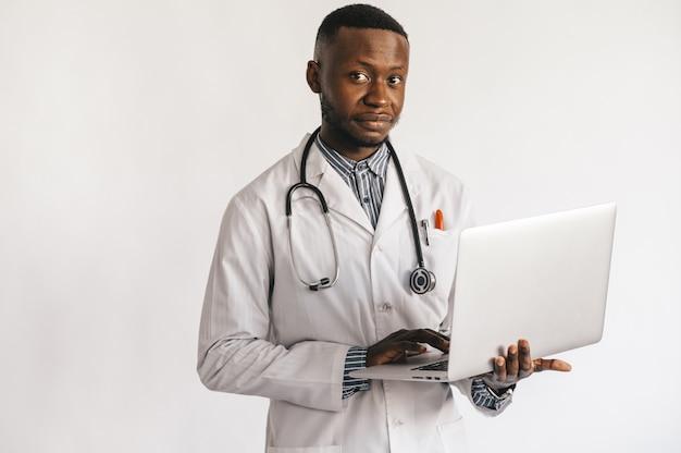 Medico giovane dalla pelle nera sorridente in piedi su uno sfondo bianco con un computer portatile nelle sue mani.