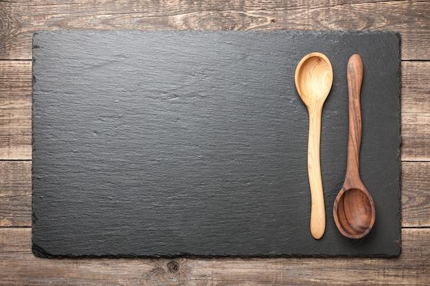 Tavola di ardesia nera con cucchiai di legno su tavola di legno