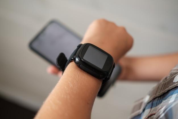Orologio smart nero sulla mano del ragazzo e smartphone nero nell'altra