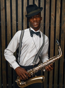 Il musicista jazz sorridente nero posa con il sassofono. il jazzista nero in cappello posa con lo strumento