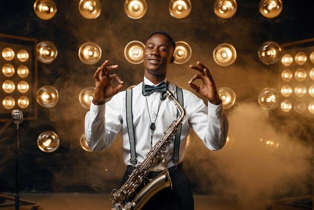 L'attore jazz sorridente nero con il sassofono mostra il segno ok sul palco con i riflettori. jazzman nero che si esibisce sulla scena