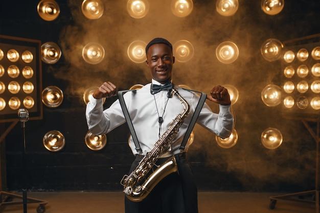 Esecutore jazz sorridente nero con sassofono sul palco con faretti. jazzman nero che si esibisce sulla scena
