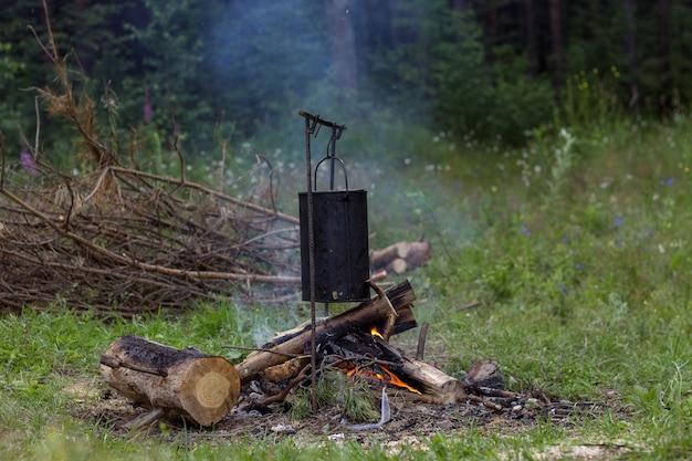 Pentola affumicata nera che bolle su un falò nel campeggio più focoso in estate