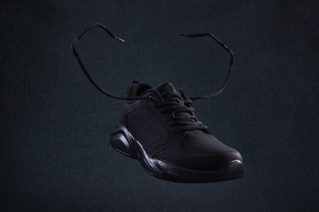 Sneaker nera con lacci che volano su sfondo scuro. le scarpe da corsa sportive nere levitano nell'aria.