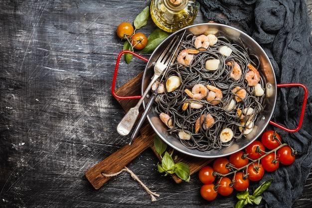 Spaghetti neri con gamberi e capesante in padella su fondo nero