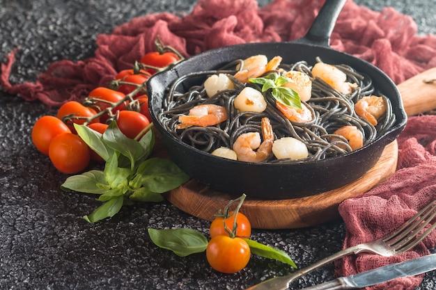 Spaghetti neri con gamberi e capesante in padella