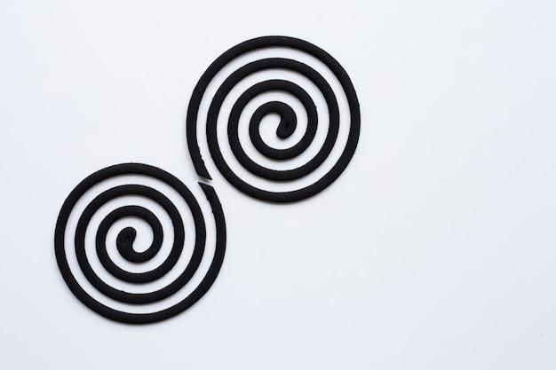 Bobine repellenti della zanzara a spirale nere su fondo bianco.
