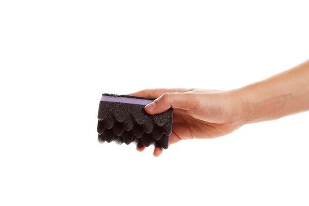 Spugna nera per piatti in mano isolati su sfondo bianco.