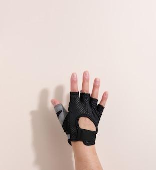 Guanto sportivo nero su una mano femminile, fondo beige. una parte del corpo è sollevata