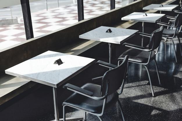 Sedie in acciaio nero e tavolo quadrato in granito bianco vicino alla finestra di vetro con luce solare diretta.