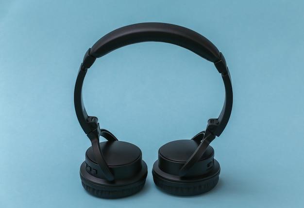 Le cuffie stereo nere stanno su sfondo blu