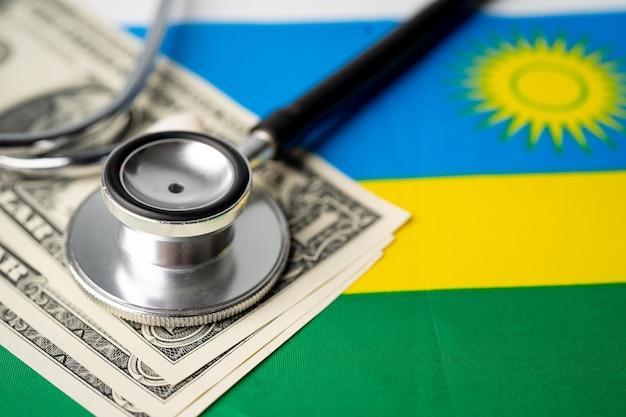 Stetoscopio nero sulla bandiera del ruanda con banconote in dollari concetto di affari e finanza