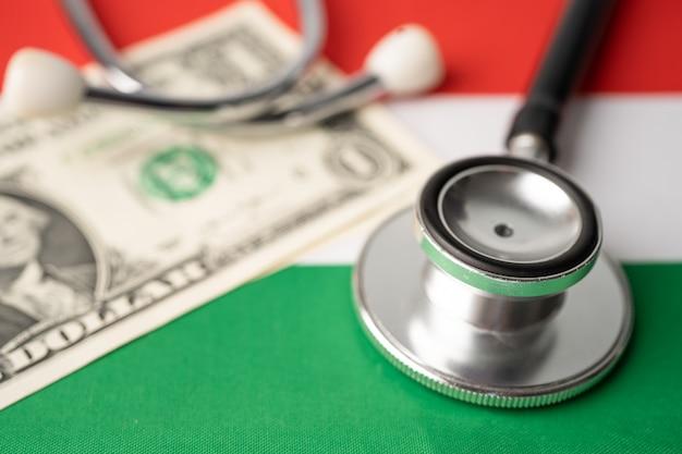 Stetoscopio nero con banconota in dollari usa sulla bandiera dell'ungheria