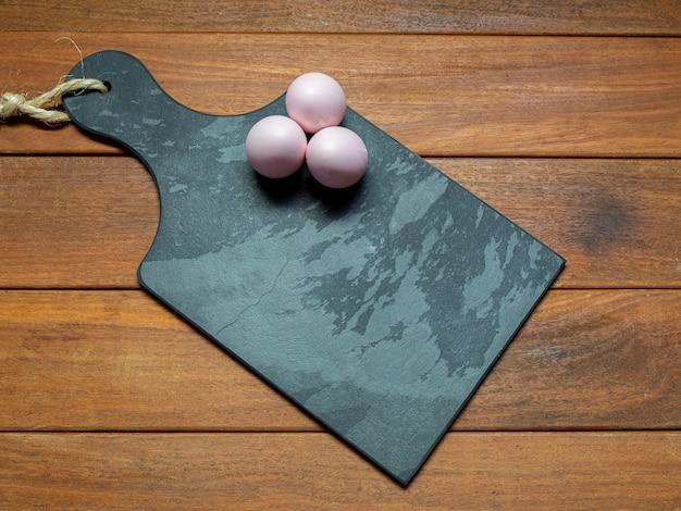 Tavola di pietra nera con uova di pasqua con spazio per il testo
