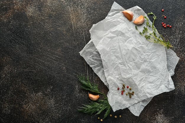 Sfondo di cottura in pietra nera. pezzo di vecchia carta da forno, spezie e verdure