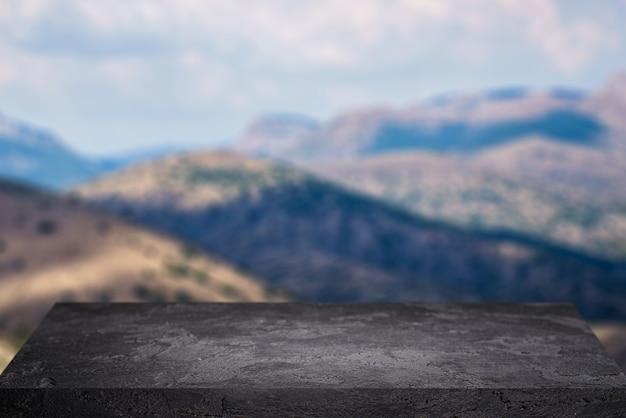 Superficie di pietra nera su sfondo di altopiani con cielo blu