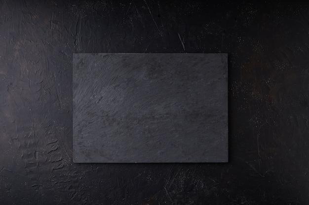 Vassoio di pietra nera su uno spazio di copia nero foto scura mock up