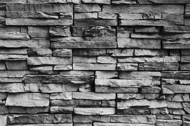 Sfondo di muro di pietra nera per il design nel tuo concetto di lavoro.