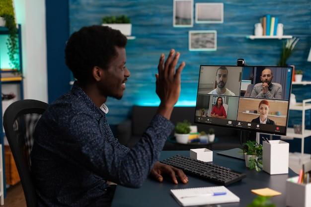 Studente nero con webinar online che saluta insegnanti a distanza