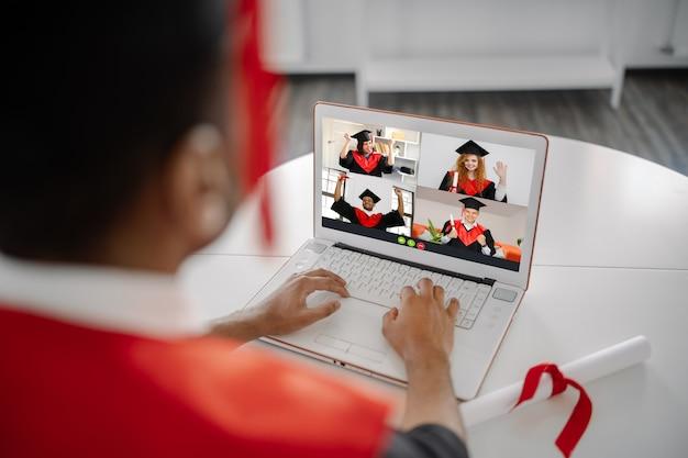 Uno studente nero si siede a un laptop con indosso un abito e un berretto quadrato e comunica con i compagni laureati cerimonia virtuale di laurea e convocazione schermo del laptop con studenti felici
