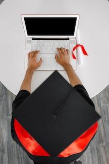 Uno studente nero siede a un laptop con indosso un abito e un berretto quadrato cerimonia virtuale di laurea e convocazione