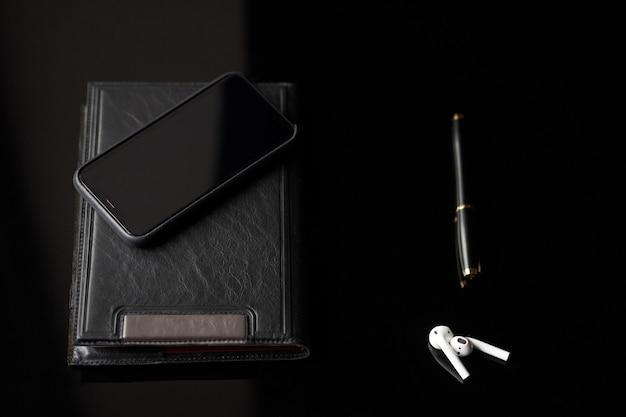 Diario alla moda nero, telefono, matita e cuffie bluetooth bianche che si trovano sul fondo nero.