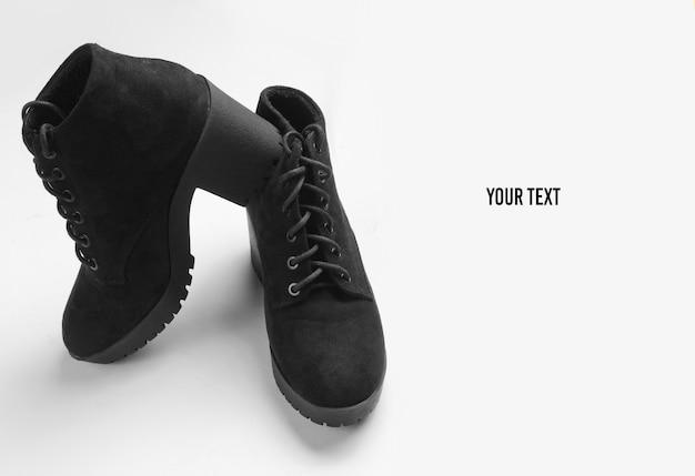 Stivali in camoscio nero su sfondo grigio. copia spazio