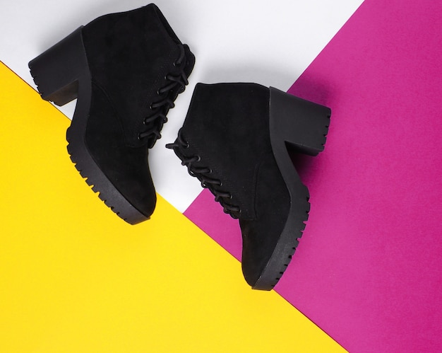 Stivali in camoscio nero su fondo di carta colorata triangolare.
