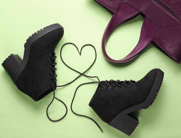 Stivale in camoscio nero con lacci a forma di cuore e borsa su fondo verde. vista dall'alto