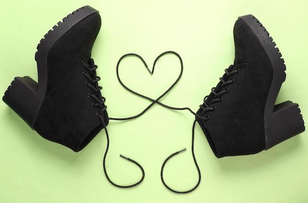 Stivale in camoscio nero con lacci a forma di cuore su sfondo verde. vista dall'alto