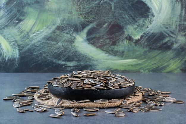 Semi di girasole neri nella ciotola sul sottopentola sulla superficie di marmo