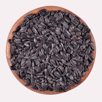 Semi di girasole neri in una ciotola di legno su sfondo bianco