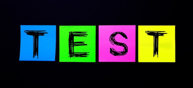 Su una superficie nera, adesivi multicolori luminosi con la parola test