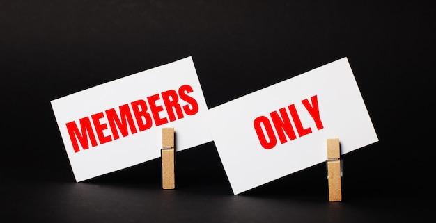 Su una superficie nera su mollette di legno, due carte bianche bianche con il testo members only