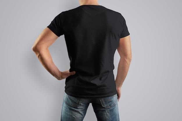 Maglietta nera su un uomo forte indietro in blue jeans. isolato su un muro grigio.