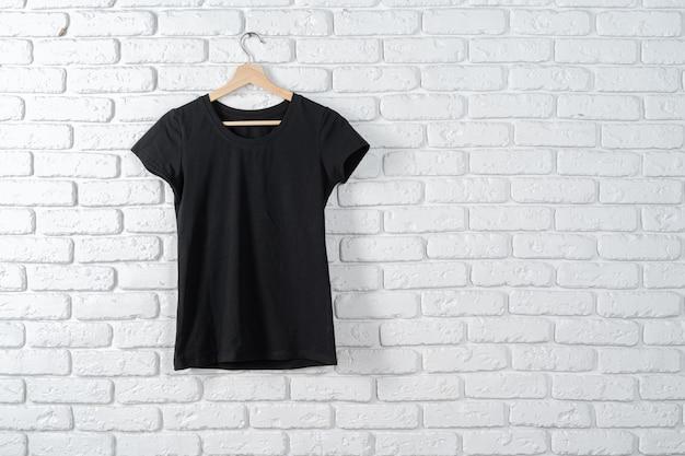 Maglietta nera che appende su un gancio contro il muro di mattoni