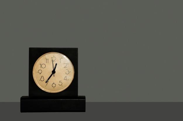 Orologio da tavolo nero con quadrante bianco in piedi su tavolo scuro isolato su sfondo scuro