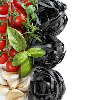 Tagliatelle nere con pomodorini, aglio ed erbe aromatiche isolate su bianco si chiuda