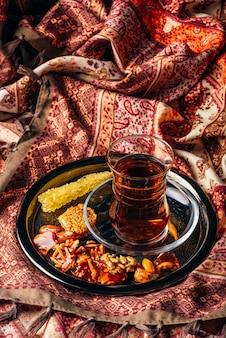 Tè nero in vetro armudu con caramelle con diverse noci e zucchero di cristallo su vassoio di metallo sopra la tovaglia