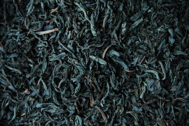 Le foglie secche del tè nero si chiudono sullo sfondo