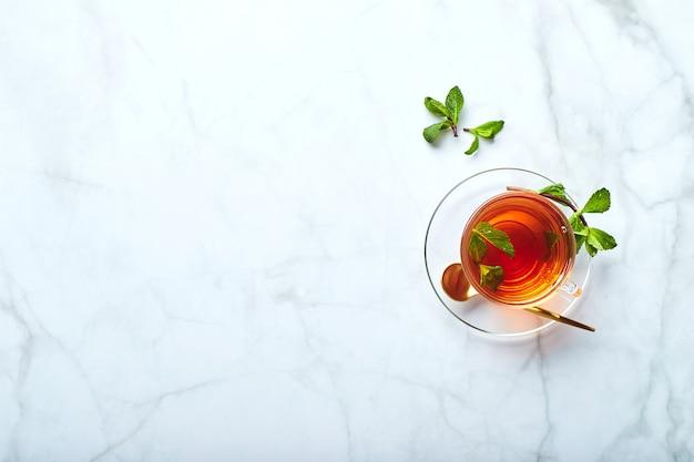 Tè nero in tazza di vetro trasparente con foglie di menta tè lenitivo antistress