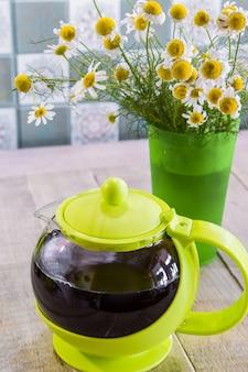 Tè nero in una tazza verde su fondo di legno e camomilla