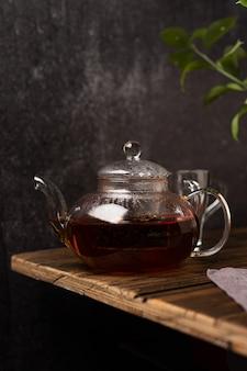 Tè nero in una teiera su uno sfondo scuro