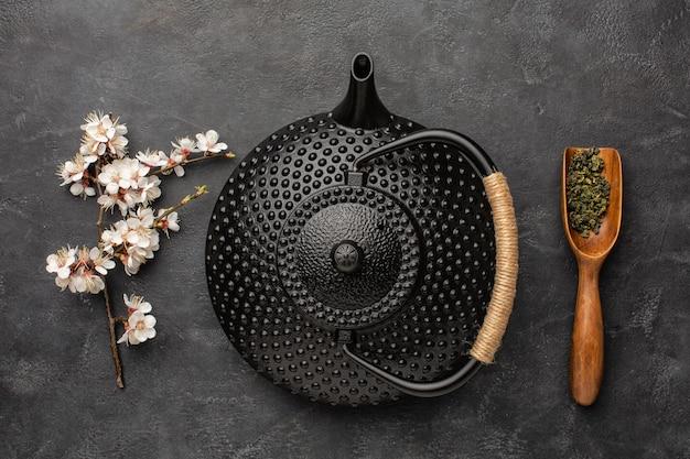 Teiera nera con ramo di sakura e tè verde su sfondo scuro.