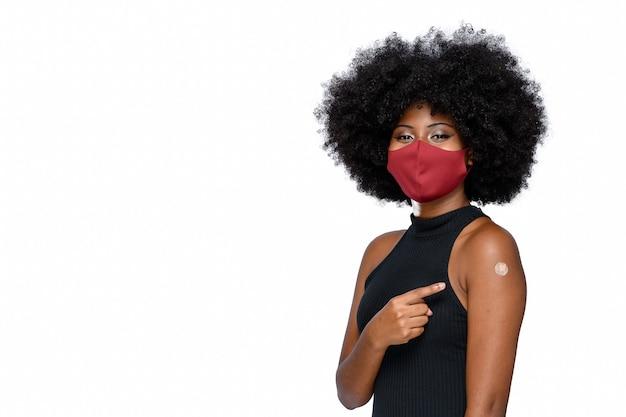 L'adolescente nero che indossa una maschera protettiva contro il covid19 mostra il marchio del vaccino